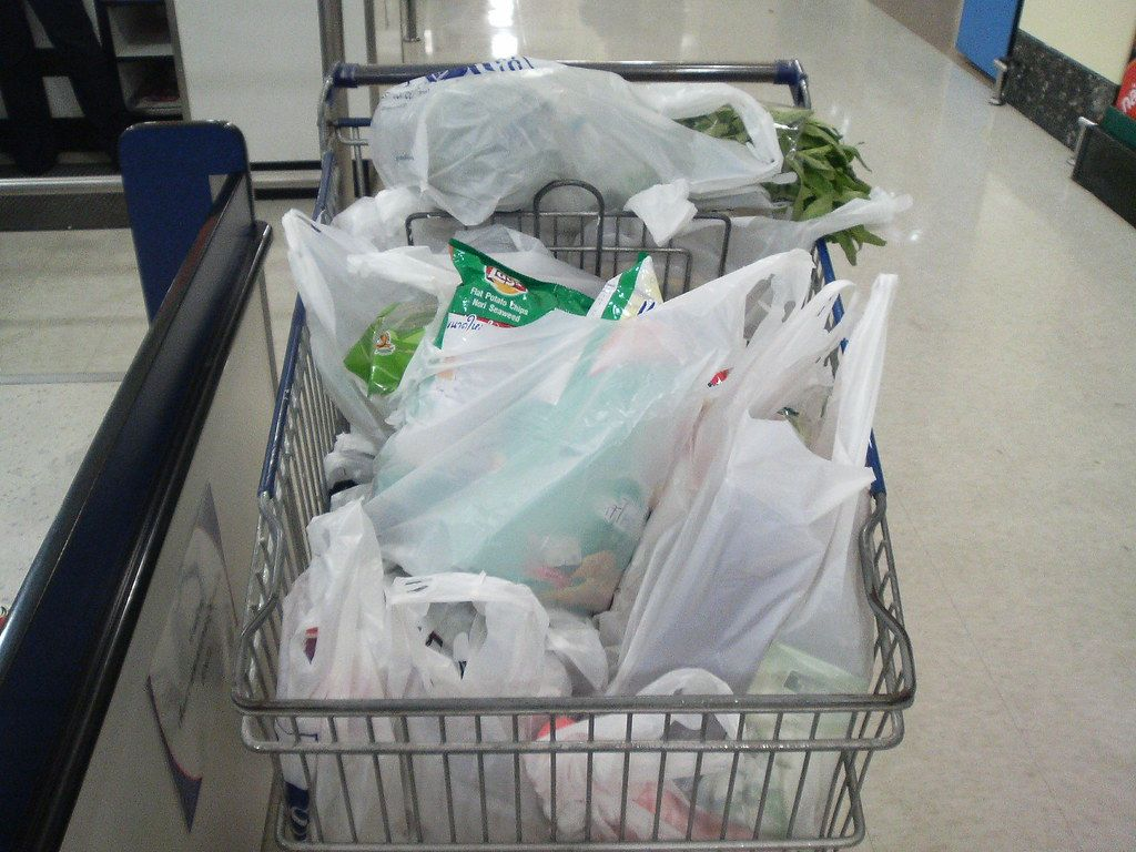 A shopping cart full of groceries in plastic bags